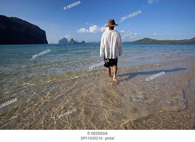 a male tourist walks in the shallow water along the coast of a small island near el nido, bacuit archipelago, palawan, philippines