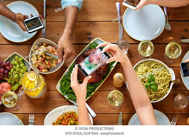 people with smartphones photographing food