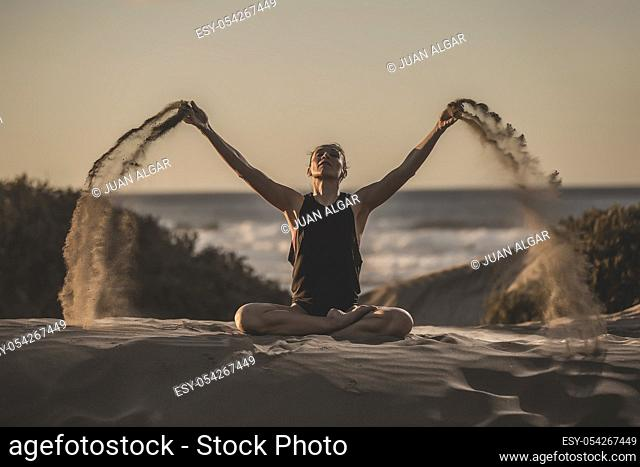 Sensual woman sitting in meditation pose while pouring heaps of sand in sunlight
