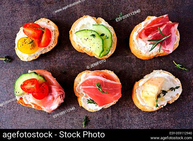 Variety of cream cheese crostini appetizers with a selection of toppings. Top view on a dark stone background. Party food concept