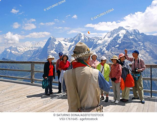 Man taking picture of Japanese tourists on viewing deck at Birg on the way to Schilthorn Canton Bernese Switzerland