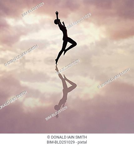 Reflection of woman dancing in cloudy sky