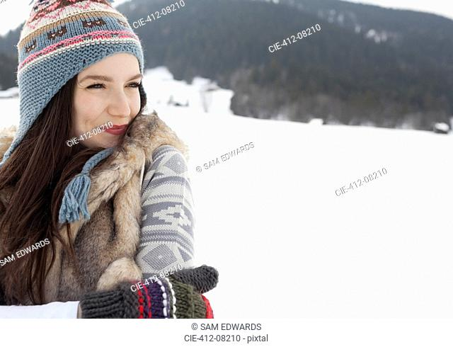 Happy woman wearing knit hat and gloves in snowy field