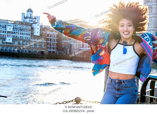 Portrait of young woman outdoors, jumping for joy, London, England, UK