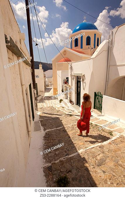 Woman in front of a colorful church in Hora, Serifos, Cyclades Islands, Greek Islands, Greece, Europe