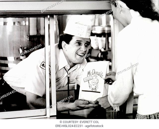 McDonald's restaurant crew member at the window handing a customer a bag. 1950s. McDonald's Corp. photo., Photo by:Everett CollectionBSLOC-2011-6-180
