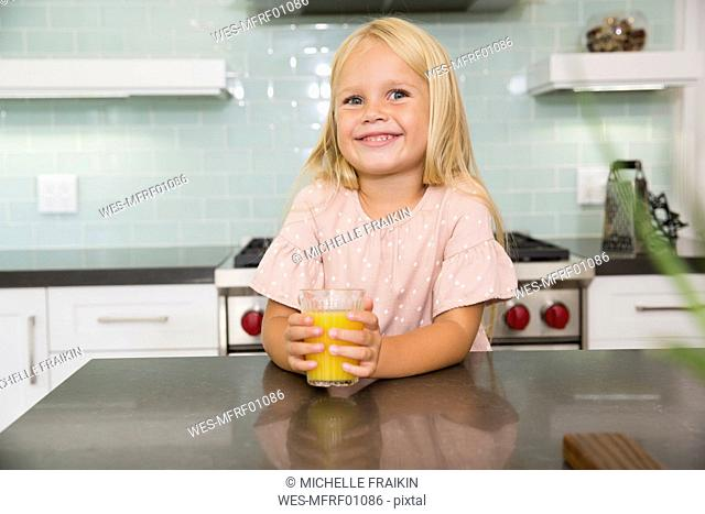 Portrait of smiling girl in kitchen with glass of orange juice