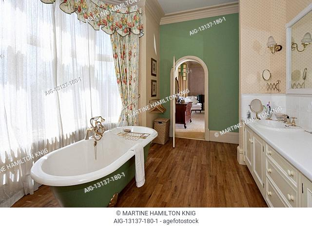 Ensuite bathroom with roll top bath, wooden floor an window drapes