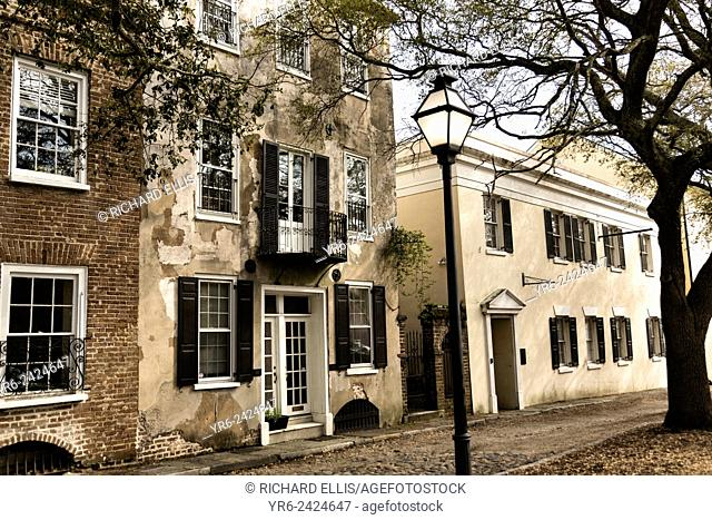 Traditional stuccoed homes and cobblestone on Gillion Street in historic Charleston, SC