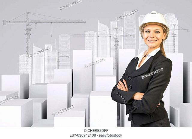 Business woman in suit and helment with crossed arms, looking at camera, smiling. Many white cubes with wire-frame buildings and tower cranes on gray background