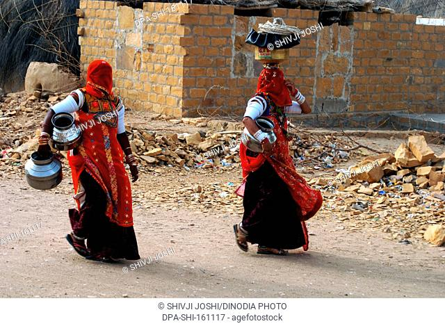 Two Rajasthani Marwari village women with pots going to well to fetch water ; Khuhri ; Jaisalmer ; Rajasthan ; India NO MR