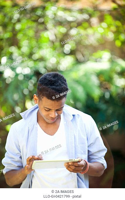 Young man working on digital tablet in park, Johannesburg, South Africa