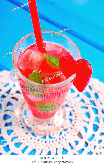 watermelon drink with mint and ice cubes on blue wooden background