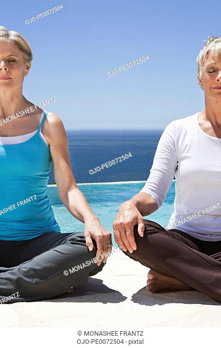 Women meditating at poolside overlooking ocean