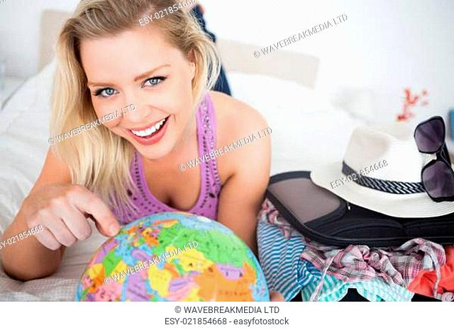 Beautiful woman with a suitcase pointing on a globe while lying on her bed