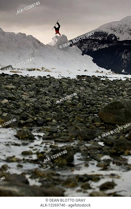 Snowboarder makes a jump on a snow hill with rocks in the foreground, Haines, Southeast Alaska