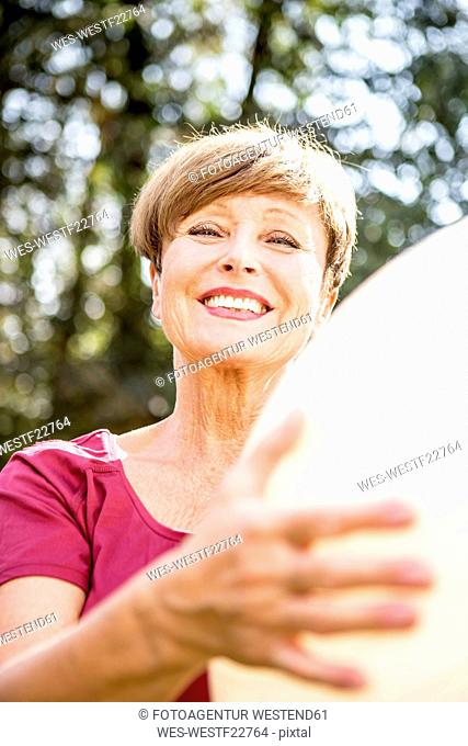 Portrait of smiling senior woman holding fitness ball outdoors