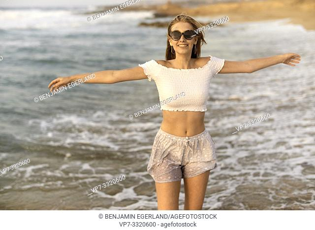 young sanguine teenage woman with open arms at beach, wet clothes, holiday, in Crete, Greece