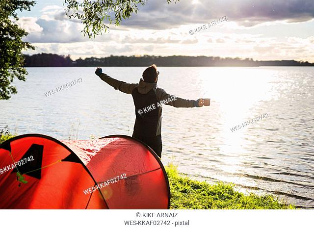 Man camping in Estonia, stretching at lake