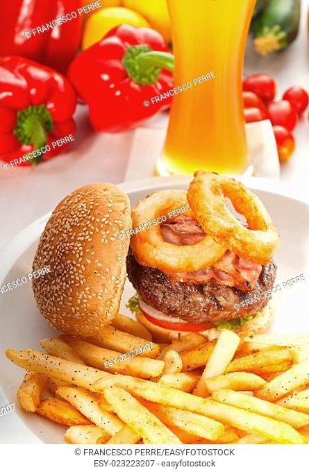 classic american hamburger sandwich with onion rings and french fries, glass of beer and fresh vegetables on background