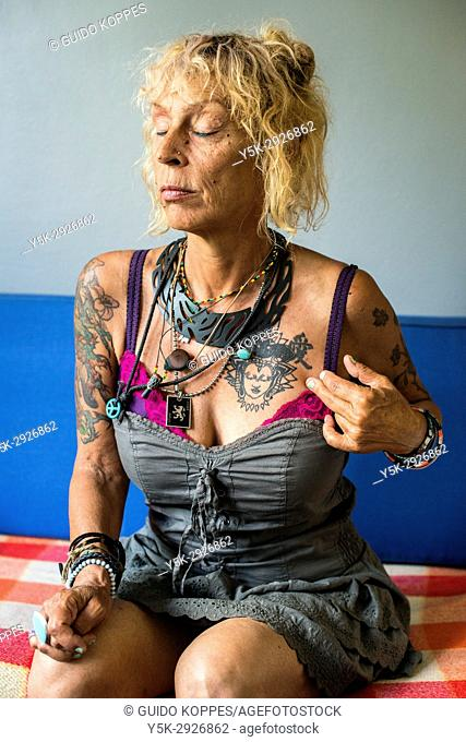 Tilburg, Netherlands. Mature adult caucasian woman with tattoo's, portrait, while sitting on a living room sofa