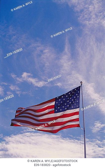 U.S. flag waving against blue sky with cirrus clouds. USA
