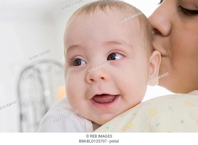 Hispanic mother kissing baby boy