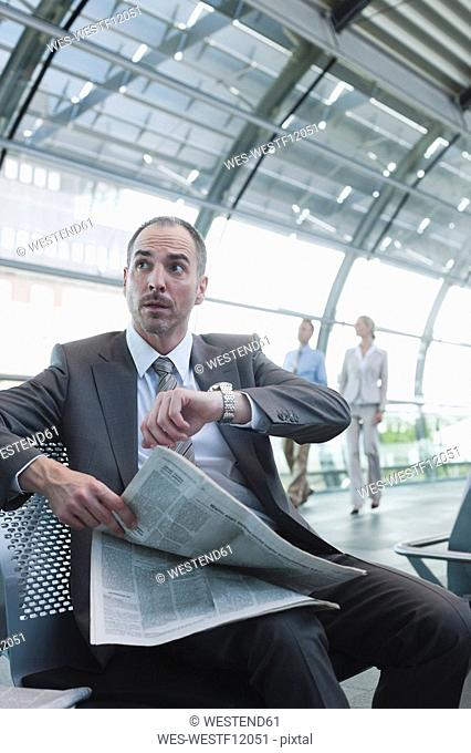 Germany, Leipzig-Halle, Airport, Businessman with newspaper, business people in background