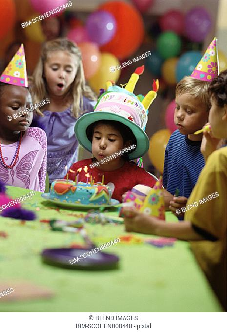 Boy blowing out birthday candles at party