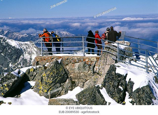 People at the Lomnicky Stit viewpoint with views across snowy peaks of the High Tatras mountains and drifting cloud