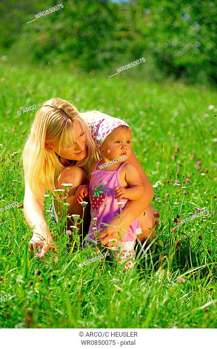 Young mother with daughter in meadow