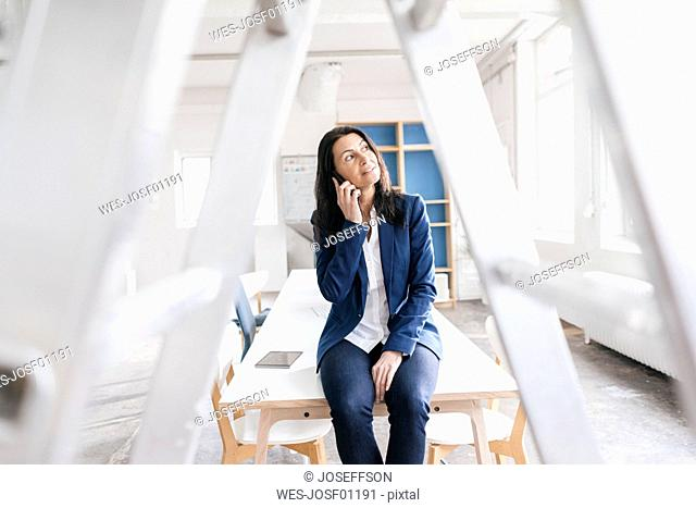 Businesswoman on the phone sitting on desk in a loft