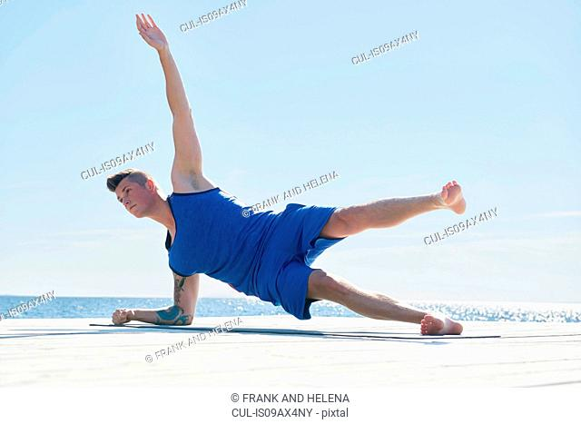 Man on pier resting on elbow, arm raised doing side push up