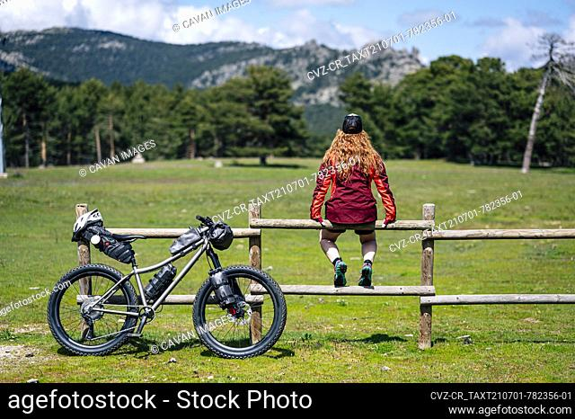 Woman enjoying with a mountain bike in nature, practices bikepacking