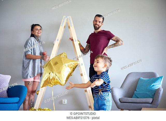 Modern family decorating the home at Christmas time using ladder as Christmas tree
