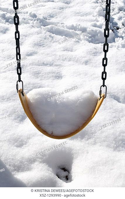 A swing full of snow in the Winter