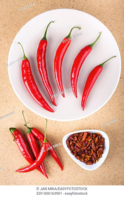 Fresh and dried red hot chili peppers on wooden background