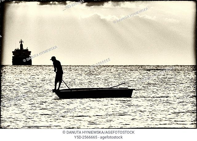 Africa, Mascarene , Mascarene Islands , Mascarenhas , Mauritius, Mauritius, Western Coast near Port Louis, single man fishing directly from the boat in shallow...