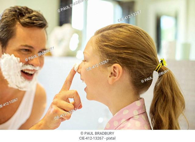 Father and daughter playing with shaving cream in bathroom