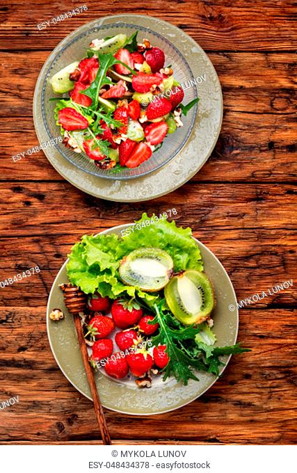 Bowl of salad with strawberry, arugula and kiwi on wooden table.Fresh spring salad