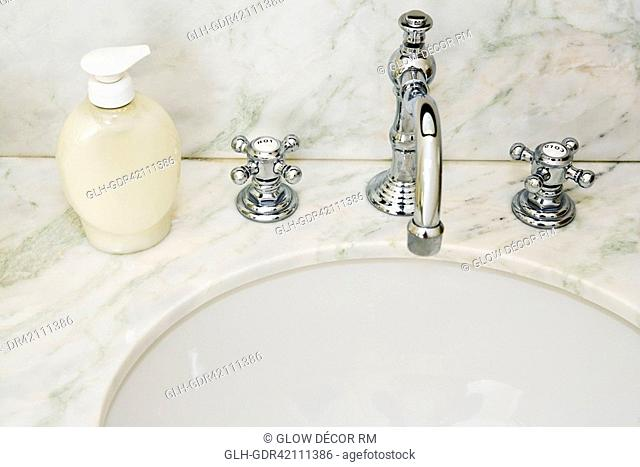 Faucet with soap dispenser near a wash bowl