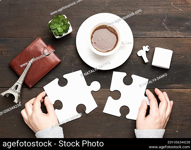 white cup with cocoa and two female hands holding white puzzle pieces on a brown wooden background, top view