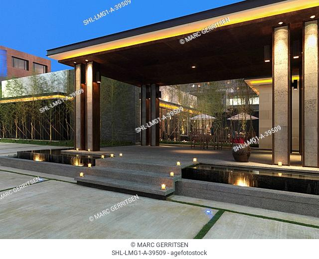 Covered stone patio with steps over infinity pool