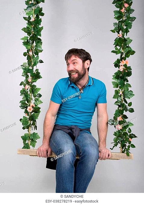 bearded man in jeans, swinging on swings and hamming to the camera. wooden swing suspended from a rope hemp, rope wrapped vine and ivy