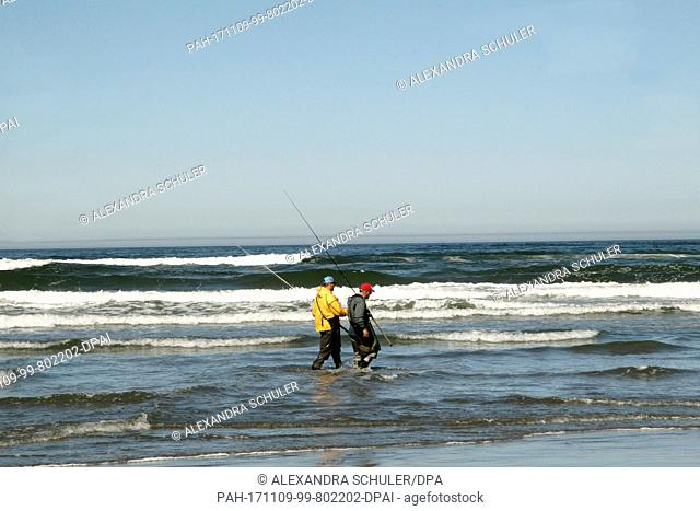 Two hobby fishermen walk through the waves on Cannon Beach, US, 2 September 2017. Cannon Beach is a small town in Clatsop County, Oregon