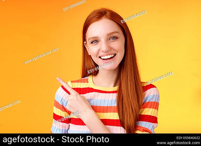 Friendly outgoing good-looking ginger girl university student discussing lecture classmate smiling laughing pointing upper left corner questioned curious know...