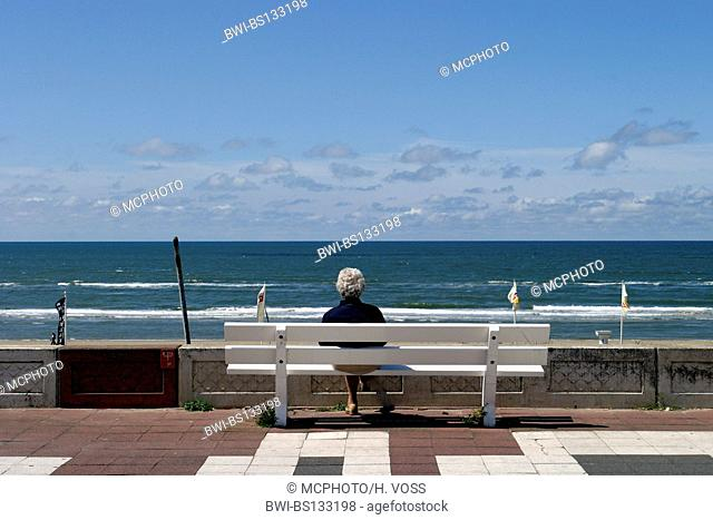 view from the beach promenade on the sea with a older woman on a bench in the foreground, Netherlands, Zandvoort