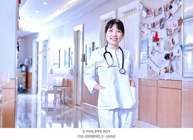 Portrait of doctor in hospital corridor looking at camera smiling