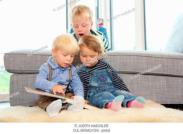 Boy and two toddlers reading childrens book on living room floor