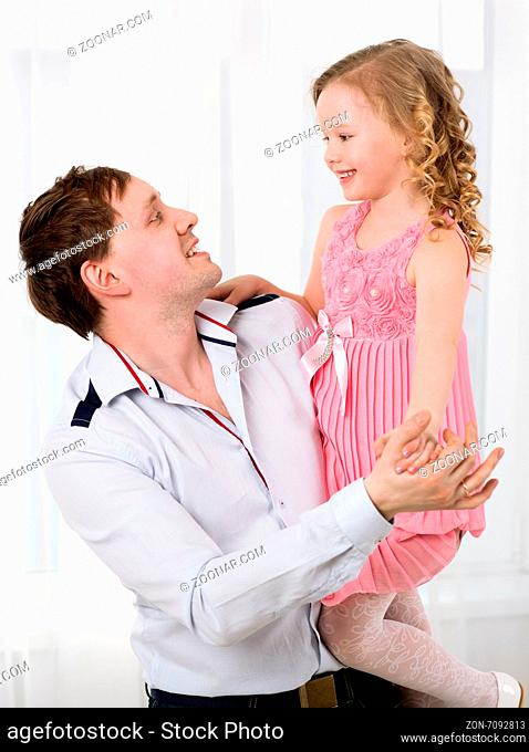 Young happy father holding beautiful little daughter in his arms and they dancing